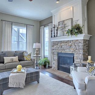 Esempio di un soggiorno american style aperto e di medie dimensioni con pareti grigie, parquet scuro, camino classico, cornice del camino in pietra, nessuna TV e pavimento marrone