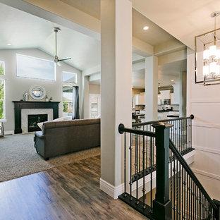 ソルトレイクシティの中サイズのトラディショナルスタイルのおしゃれなファミリールーム (白い壁、無垢フローリング、タイルの暖炉まわり、標準型暖炉、茶色い床) の写真