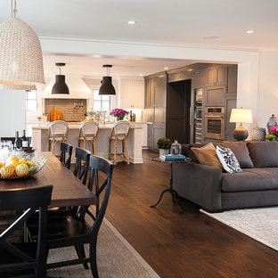 Example of a mid-sized farmhouse open concept dark wood floor and brown floor family room design in San Diego with white walls, a standard fireplace, a wood fireplace surround and a wall-mounted tv