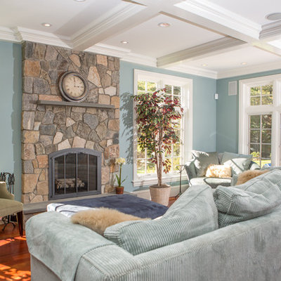Inspiration for a mid-sized timeless open concept medium tone wood floor and brown floor family room remodel in Boston with blue walls, a standard fireplace, a stone fireplace and no tv
