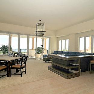Réalisation d'une grande salle de séjour ethnique ouverte avec un mur blanc, un sol en bois clair, aucune cheminée, un téléviseur encastré et un sol beige.