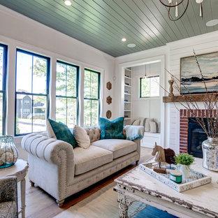 Foto de sala de estar abierta, de estilo de casa de campo, extra grande, con paredes blancas, suelo de madera clara, chimenea tradicional, marco de chimenea de ladrillo, televisor colgado en la pared y suelo marrón