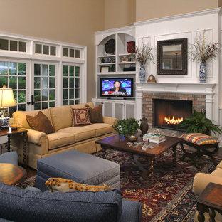 他の地域の大きいトラディショナルスタイルのおしゃれなファミリールーム (ベージュの壁、濃色無垢フローリング、標準型暖炉、レンガの暖炉まわり、据え置き型テレビ) の写真