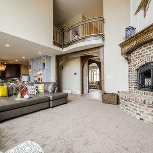 Esempio di un grande soggiorno stile americano aperto con pareti grigie, moquette, camino ad angolo, cornice del camino in mattoni e TV a parete