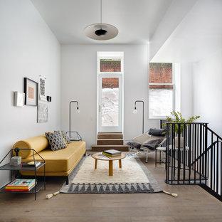 Esempio di un grande soggiorno design stile loft con sala giochi, pareti bianche, pavimento in laminato, nessun camino, nessuna TV e pavimento marrone