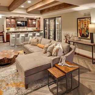 Modelo de sala de estar con barra de bar abierta, rústica, grande, con suelo de madera en tonos medios, suelo beige, paredes blancas, chimenea lineal, marco de chimenea de yeso y televisor colgado en la pared