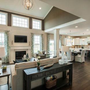 Imagen de sala de estar abierta, clásica renovada, grande, con suelo de madera oscura, paredes multicolor, chimenea tradicional, marco de chimenea de yeso y televisor colgado en la pared