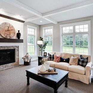 Foto de sala de estar cerrada, campestre, grande, con paredes beige, moqueta, chimenea tradicional, marco de chimenea de piedra y suelo beige