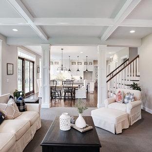 Modelo de sala de estar cerrada, de estilo de casa de campo, grande, con paredes beige, moqueta, chimenea tradicional, marco de chimenea de piedra y suelo beige