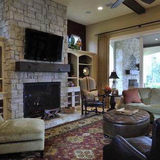 Foto di un grande soggiorno tradizionale aperto con TV a parete, pareti marroni, camino classico, cornice del camino in pietra, pavimento in travertino e pavimento beige