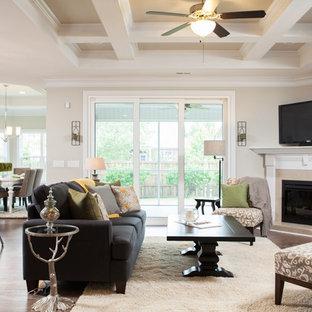 Foto di un soggiorno classico con pavimento in legno massello medio, camino ad angolo, cornice del camino piastrellata e porta TV ad angolo