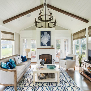 Inspiration for a beach style light wood floor family room remodel in Providence with beige walls, a standard fireplace and a tv stand