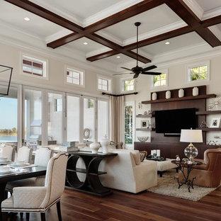 Modelo de sala de estar abierta, clásica renovada, de tamaño medio, sin chimenea, con paredes beige, suelo de madera en tonos medios, pared multimedia y suelo marrón