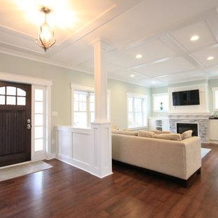 ワシントンD.C.のおしゃれなファミリールーム (青い壁、濃色無垢フローリング、標準型暖炉、石材の暖炉まわり、壁掛け型テレビ、茶色い床) の写真