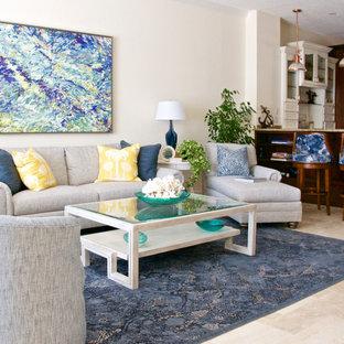 タンパの中くらいのトロピカルスタイルのおしゃれなオープンリビング (マルチカラーの壁、トラバーチンの床、横長型暖炉、石材の暖炉まわり、壁掛け型テレビ、ベージュの床) の写真