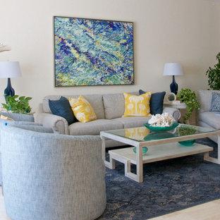 タンパの中サイズのトロピカルスタイルのおしゃれなファミリールーム (マルチカラーの壁、トラバーチンの床、横長型暖炉、石材の暖炉まわり、壁掛け型テレビ、ベージュの床) の写真