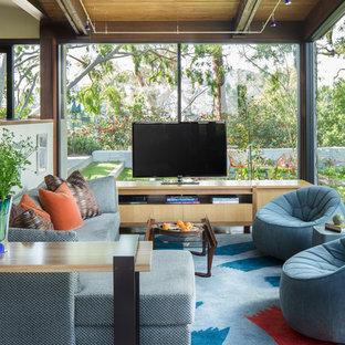 Cette photo montre une grande salle de séjour tendance ouverte avec un téléviseur indépendant, béton au sol et un sol bleu.
