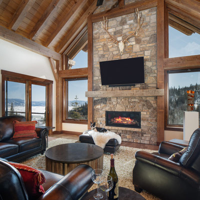 Example of a mountain style medium tone wood floor family room design in Denver with white walls, a ribbon fireplace, a stone fireplace and a wall-mounted tv