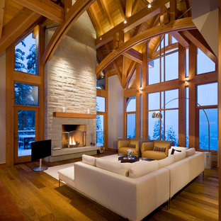 Inspiration for a large rustic open concept medium tone wood floor family room remodel in Vancouver with a standard fireplace, a stone fireplace, a tv stand and beige walls