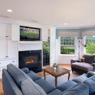 ニューヨークの中サイズのトラディショナルスタイルのおしゃれな独立型ファミリールーム (青い壁、内蔵型テレビ、無垢フローリング、標準型暖炉、金属の暖炉まわり、ベージュの床) の写真