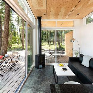 Modelo de sala de estar abierta, rural, pequeña, con paredes blancas, suelo de cemento, estufa de leña y suelo gris