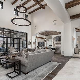 フェニックスの巨大なインダストリアルスタイルのおしゃれなオープンリビング (ベージュの壁、濃色無垢フローリング、標準型暖炉、石材の暖炉まわり、壁掛け型テレビ、マルチカラーの床) の写真