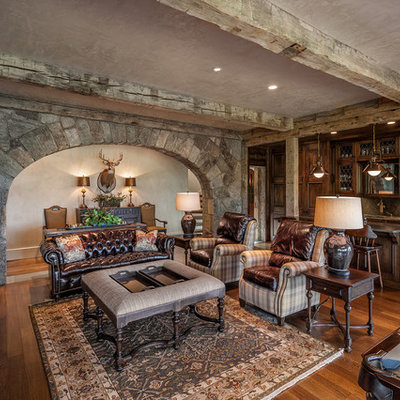 Example of a large tuscan open concept medium tone wood floor and brown floor family room design in Other with gray walls, a standard fireplace, a stone fireplace and a wall-mounted tv