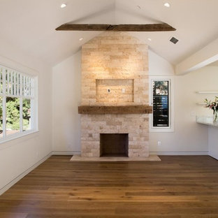 This is an example of a mid-sized arts and crafts open concept family room in New York with white walls, medium hardwood floors, a standard fireplace, a stone fireplace surround and brown floor.
