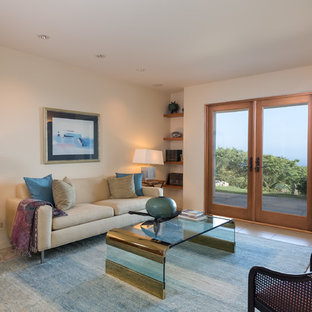 Photo of a mid-sized transitional enclosed family room in Santa Barbara with white walls, ceramic floors, no fireplace, a wall-mounted tv and beige floor.