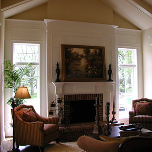 Example of a mid-sized classic enclosed dark wood floor family room design in St Louis with beige walls, a standard fireplace, a wood fireplace surround and no tv