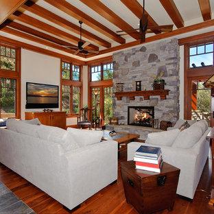 オレンジカウンティの広いおしゃれな独立型ファミリールーム (壁掛け型テレビ、濃色無垢フローリング、標準型暖炉、石材の暖炉まわり、グレーの壁) の写真