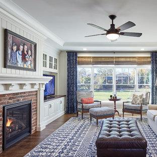 シカゴのトランジショナルスタイルのおしゃれな独立型ファミリールーム (白い壁、濃色無垢フローリング、標準型暖炉、レンガの暖炉まわり、据え置き型テレビ、茶色い床) の写真