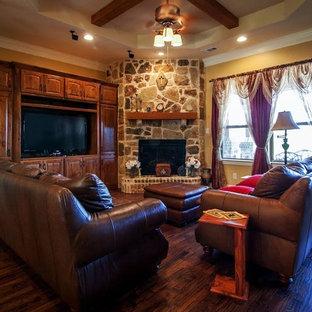 ダラスの中サイズのトラディショナルスタイルのおしゃれなファミリールーム (黄色い壁、無垢フローリング、コーナー設置型暖炉、石材の暖炉まわり、埋込式メディアウォール) の写真