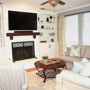 中サイズのトラディショナルスタイルのおしゃれなオープンリビング (青い壁、ラミネートの床、標準型暖炉、レンガの暖炉まわり、壁掛け型テレビ、茶色い床) の写真