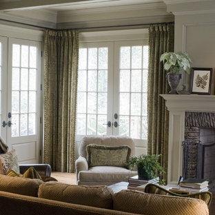 Diseño de sala de estar tradicional con paredes beige, chimenea tradicional y marco de chimenea de piedra