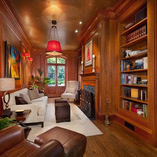 Idee per un soggiorno chic chiuso e di medie dimensioni con parquet scuro, libreria, pareti marroni, camino classico, cornice del camino in legno e nessuna TV