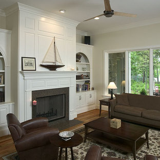 Inspiration for a timeless medium tone wood floor family room remodel in Charlotte with beige walls, a standard fireplace and no tv