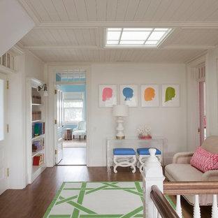ニューヨークの中サイズのトラディショナルスタイルのおしゃれなファミリールーム (白い壁、濃色無垢フローリング、埋込式メディアウォール、ゲームルーム、暖炉なし、茶色い床) の写真