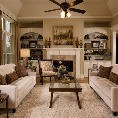 Inspiration for a timeless medium tone wood floor family room remodel in San Diego with beige walls, a standard fireplace, a stone fireplace and no tv