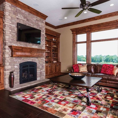 Example of a classic dark wood floor family room design in Other with beige walls, a standard fireplace, a stone fireplace and a wall-mounted tv