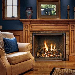 シアトルの大きいトラディショナルスタイルのおしゃれなファミリールーム (標準型暖炉、木材の暖炉まわり、青い壁、無垢フローリング、茶色い床) の写真