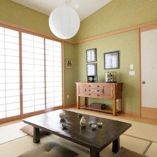Idées déco pour une grand salle de séjour asiatique fermée avec un mur vert, un téléviseur dissimulé, un sol en bois clair et aucune cheminée.