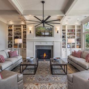 他の地域の大きいトラディショナルスタイルのおしゃれなファミリールーム (グレーの壁、標準型暖炉、石材の暖炉まわり、壁掛け型テレビ、コンクリートの床、マルチカラーの床) の写真