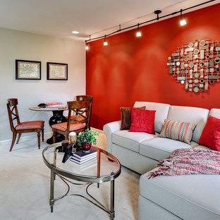 Modelo de sala de juegos en casa tradicional, pequeña, con paredes rojas, moqueta y televisor colgado en la pared