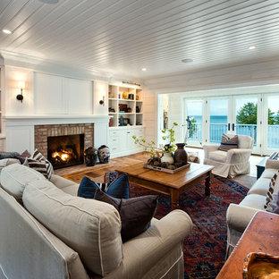 Réalisation d'une salle de séjour tradition de taille moyenne et ouverte avec télé d'angle, un mur blanc, un sol en bois brun, une cheminée standard, un manteau de cheminée en brique et un sol marron.