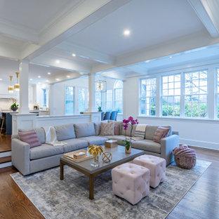 Réalisation d'une grand salle de séjour tradition ouverte avec un sol en bois foncé, une cheminée standard, un manteau de cheminée en bois, un téléviseur fixé au mur, un sol marron, un plafond à caissons et un mur blanc.