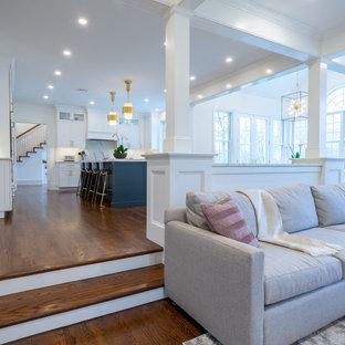 Großes, Offenes Klassisches Wohnzimmer mit weißer Wandfarbe, dunklem Holzboden, Kamin, Kaminumrandung aus Holz, Wand-TV, braunem Boden und Kassettendecke in Philadelphia
