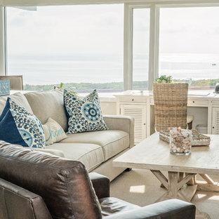 Modelo de sala de estar cerrada, costera, de tamaño medio, sin televisor, con paredes beige, suelo de travertino, chimenea tradicional, suelo beige y marco de chimenea de piedra