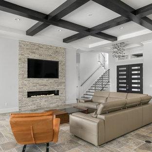 Inspiration pour une grande salle de séjour minimaliste ouverte avec un mur gris, un sol en travertin, une cheminée ribbon, un manteau de cheminée en pierre, un téléviseur fixé au mur et un sol gris.