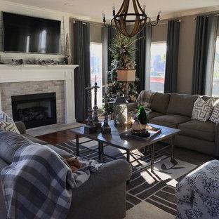 Diseño de sala de estar cerrada, campestre, de tamaño medio, con paredes grises, suelo de madera oscura, chimenea tradicional, marco de chimenea de ladrillo y televisor colgado en la pared